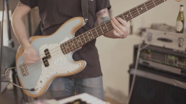 vidéos et rushes de groupe jouant dans leur studio de répétition : bassiste - rock moderne
