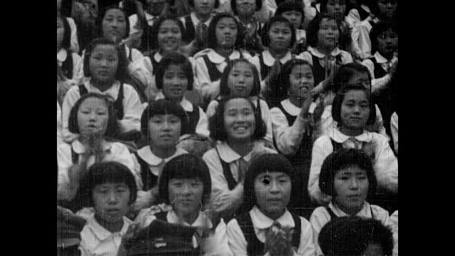 vídeos y material grabado en eventos de stock de / band plays a parade in the distance / hundreds watch as north korean sports champions march around on display / school girls clapping boys playing... - coreano oriental
