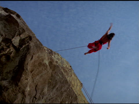 stockvideo's en b-roll-footage met bandaloop project dancer, attached to safety harness, performs acrobatic routine jumping off and onto cliff face, california - routine