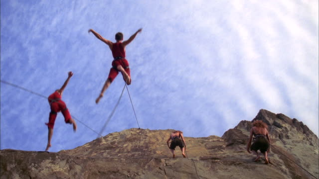 vídeos de stock e filmes b-roll de bandaloop project dancers jump and leap from cliff face, whilst attached to harnesses, california available in hd. - artista