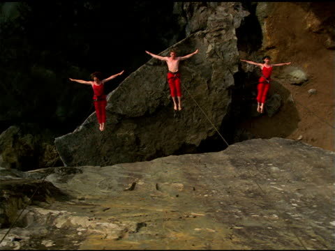 stockvideo's en b-roll-footage met bandaloop project dancers leap and jump off and onto cliff face, california - jaar 2000 stijl