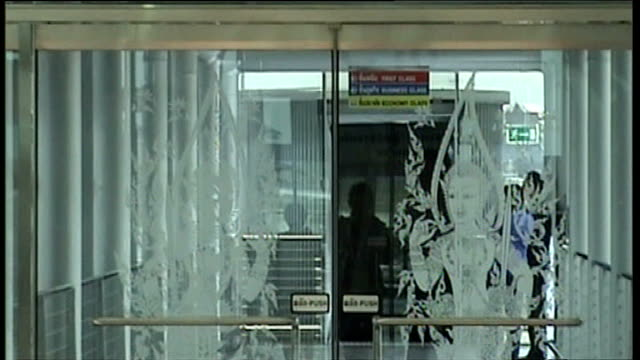 bangkok airport: int views through terminal windows showing people disembarking plane, plane boarding bridge slow motion view through airport window... - gary glitter stock videos & royalty-free footage