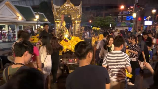 suspect goes on trial / alleged uighur people trafficking gang involvement; ext / night various shots of visitors to erawan shrine laying offerings... - エラワン聖堂点の映像素材/bロール