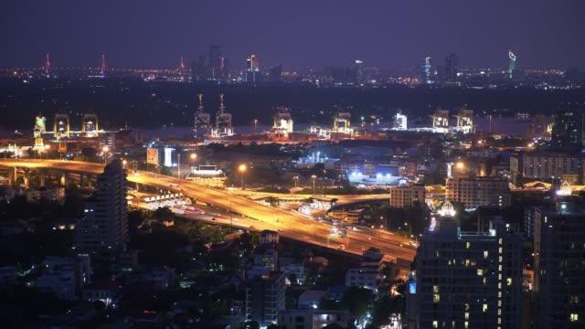 bangkok stadt in der nacht mit blick auf logistischen import und export hafen im hintergrund. blick von der spitze des gebäudes. - bangkok stock-videos und b-roll-filmmaterial