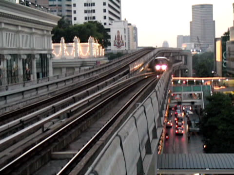 bangkok elevated skytrain glides above traffic, early dusk: thailand - elevated train stock videos & royalty-free footage