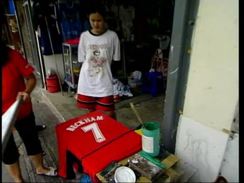bangkok: ext woman printing fake david beckham number 7 shirt replica football kits displayed lib night people along busy street in red light... - number 7 stock videos & royalty-free footage