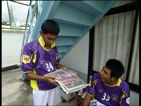 Bangkok Football player lacing up boot EXT Thai footballers getting dressed for match Footballer reading newspaper Vox pops Thai footballer LA Coach...