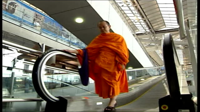 new airport delayed by military coups thailand bangkok suvarnabhumi airport int monk towards on travelator man standing next rows of parked cars low... - 固定された点の映像素材/bロール