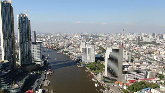 vídeos de stock e filmes b-roll de bangkok skyline with skyscrapers along the chao phraya river  / bangkok - aerial view 4k - bangkok