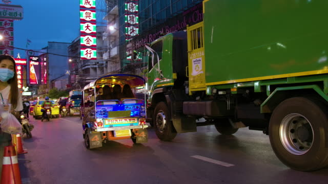 stockvideo's en b-roll-footage met bangkok, thailand -september 5, 2020 heavy traffic on yaowarat road passes below lit signs in the chinatown district at dusk. yaowarat has been the main center of chinese culture in bangkok for over 200 years. - taxi