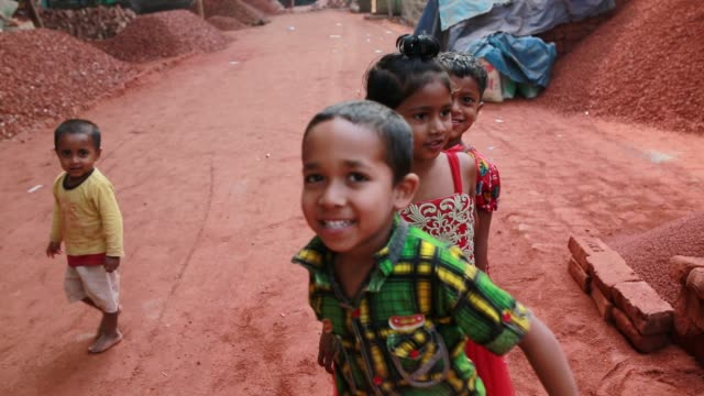 bangladeshi children play where their mother break bricks in dhaka bangladesh on march 06 2018 with over half of the population living below the... - lanci e salti femminile video stock e b–roll