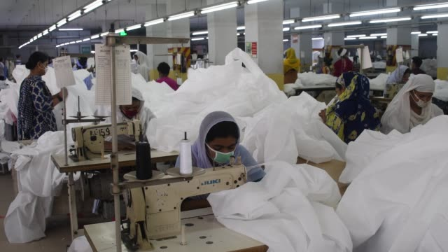 bangladeshi garment workers make protective suit at a factory amid concerns over the spread of the coronavirus disease in dhaka, bangladesh, april 1,... - manufacturing occupation stock videos & royalty-free footage