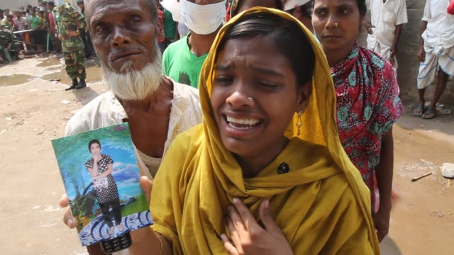 a bangladeshi girl holding a photo of her missing sister cries at savar adhar chandra high school ground near dhaka bangladesh friday 26 april 2013... - missing persons stock videos & royalty-free footage