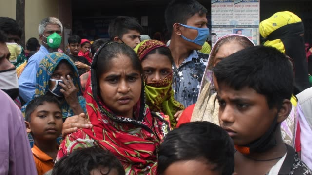 vídeos de stock e filmes b-roll de bangladeshi homeless people wait in a queue to get aid during the nationwide lockdown imposed as a measure to prevent the spread of covid19 in dhaka... - crise mundial de alimentos