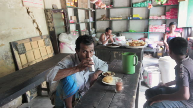bangladeshi man having a breakfast and tea at a local restaurant, sreemangal (srimangal), division of sylhet, bangladesh, indian sub-continent, asia  - teenager alter stock-videos und b-roll-filmmaterial