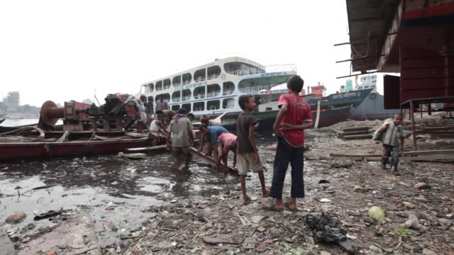 Bangladeshi men carrying a heavy piece of wood from the river at the Dhaka ship yard,  Dhaka, Bangladesh, Indian Sub-Continent, Asia