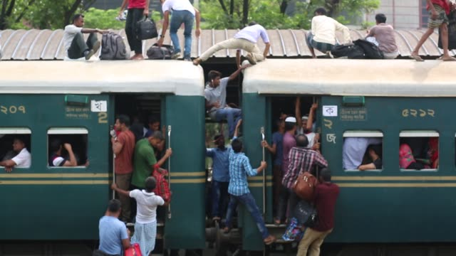 bangladeshi people board an overcrowded train travelling to to their home towns at airport station in dhaka bangladesh on june 22 2017 thousands of... - lavoratore emigrante video stock e b–roll