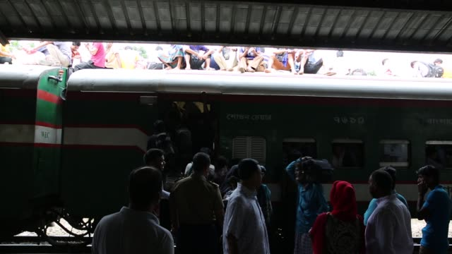 bangladeshi people board an overcrowded train travelling to to their home towns at, airport station in dhaka, bangladesh on june 22, 2017. thousands... - lavoratore emigrante video stock e b–roll