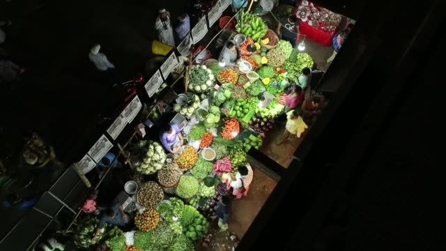 bangladeshi people browse vegetable in a street vegetable market at night in dhaka, bangladesh - nachtmarkt stock-videos und b-roll-filmmaterial