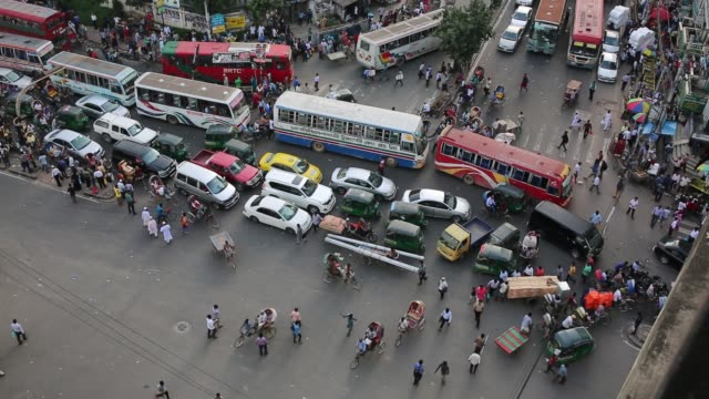 Bangladeshi people gather at an intersection in Dhaka Bangladesh on August 24 2017 / A World Bank report says the average traffic speed in Dhaka has...