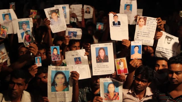bangladeshi people hold photographs of their relatives whom they believe are trapped in the rubbles of a building that collapsed in savar outskirts... - savar stock videos and b-roll footage