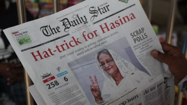 bangladeshi people read a newspaper carrying headlines of the bangladesh general election results in dhaka on december 31, 2018 - zeitschrift stock-videos und b-roll-filmmaterial