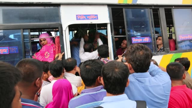 Bangladeshi people try to ride in of an overcrowded bus to travel home as others wait for transport ahead of Iftar in Dhaka Bangladesh on June 20...