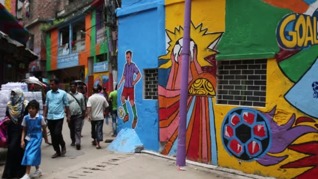 bangladeshi people walks through next to a wall painted by soccer fans during the 2018 fifa world cup in russia in dhaka , bangladesh on july 10,... - international team soccer stock videos & royalty-free footage