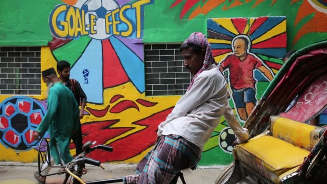 stockvideo's en b-roll-footage met bangladeshi people walks through next to a wall painted by soccer fans during the 2018 fifa world cup in russia in dhaka bangladesh on july 10 2018... - wereldkampioenschap sport