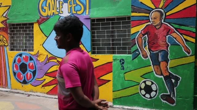 vídeos y material grabado en eventos de stock de bangladeshi people walks through next to a wall painted by soccer fans during the 2018 fifa world cup in russia in dhaka , bangladesh on july 10,... - fifa