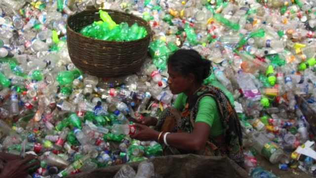 bangladeshi people work in a plastic bottle recycling factory in dhaka bangladesh on february 08 2018 after removing the labels and caps and... - lanci e salti femminile video stock e b–roll