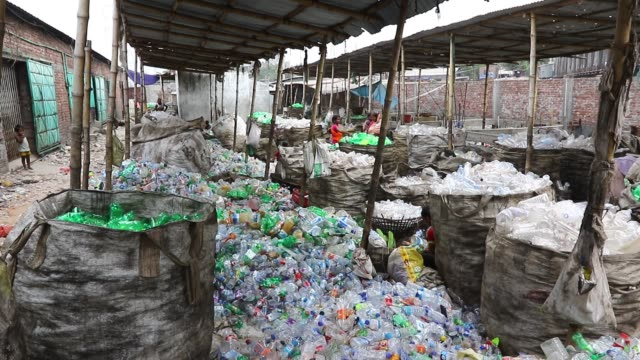 bangladeshi people work in a plastic bottle recycling factory in dhaka after removing the labels and caps and gathering the bottles in giant sacks... - lanci e salti femminile video stock e b–roll