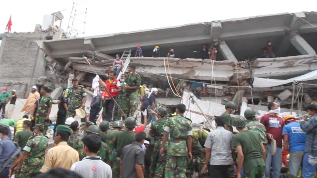 stockvideo's en b-roll-footage met bangladeshi rescue workers and civilian volunteers assist in rescue operations after an eightstorey building collapsed in savar on the outskirts of... - textielindustrie