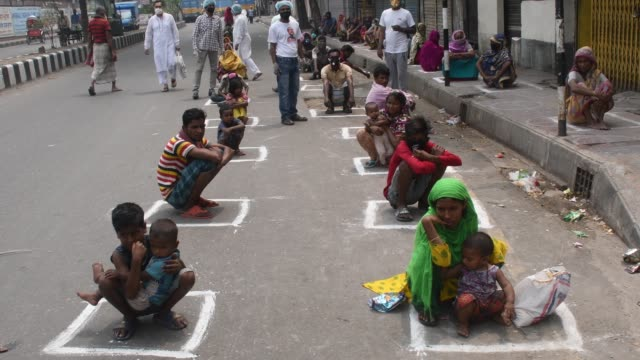 vídeos de stock e filmes b-roll de bangladeshi street peoples gathered to collect foods sit in lines adopting social distancing rules as they received relief materials provided by... - crise mundial de alimentos