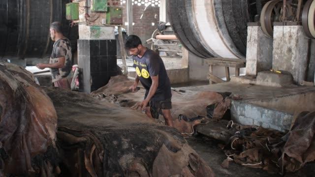 bangladeshi tannery workers process raw leather inside a factory at savar tannery area on the banks of the dhaleshwari river in savar, near dhaka. - läder bildbanksvideor och videomaterial från bakom kulisserna