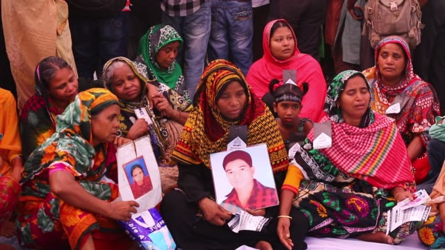 vídeos de stock e filmes b-roll de bangladeshi woman holds a picture of a relative who died in the rana plaza building collapse, as she marks the third anniversary of the disaster at... - pátio