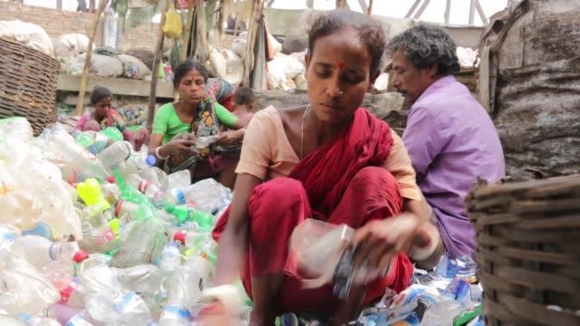 vidéos et rushes de bangladeshi women and child work in a plastic bottle recycling factory in dhaka on april 27 2019 recycling plastic bottles has become a growing... - bangladesh