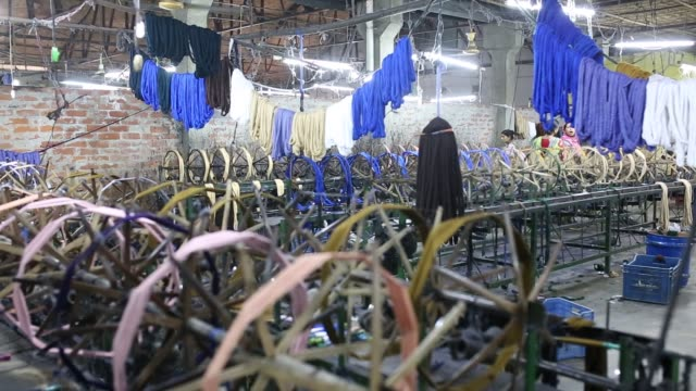 bangladeshi workers busy with making cloths inside a factory in a rural area - bangladesch stock-videos und b-roll-filmmaterial