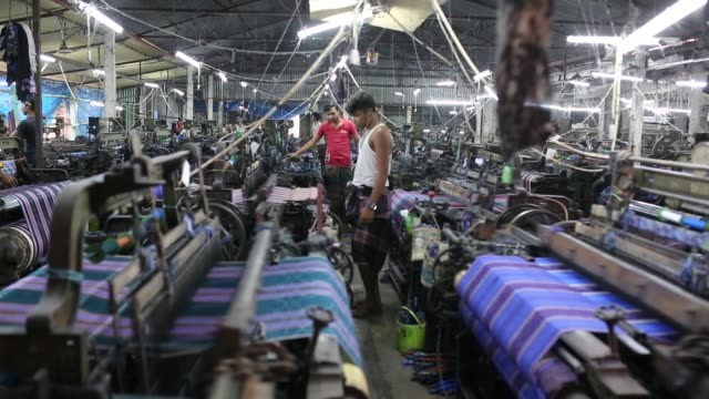 vidéos et rushes de bangladeshi workers busy with making cloths inside a factory in a rural area - chiffon