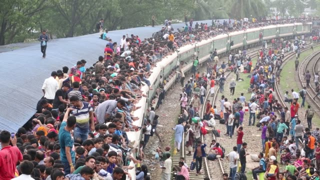 Bangladeshis cram onto a train as they travel back home to be with their families ahead of the Muslim festival of Eid alFitr in Dhaka Bangladesh on...