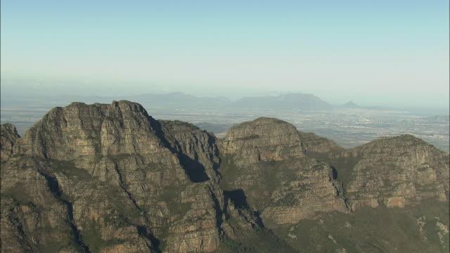 vídeos y material grabado en eventos de stock de aerial banhoek mountains, cityscape, table mountain and lion's head in distance, franschhoek, western cape, south africa - cabo winelands