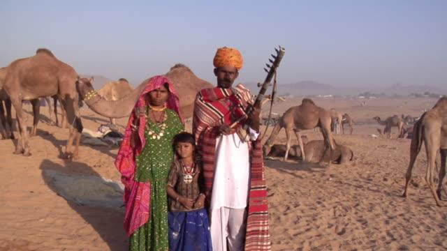 MS ZI Banjaara man, playing string instrument, with his family at Pushkar Camel Fair / Pushkar, Rajasthan, India