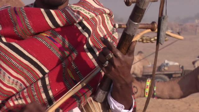 CU ZO MS Banjaara man, playing string instrument, with his family at Pushkar Camel Fair / Pushkar, Rajasthan, India