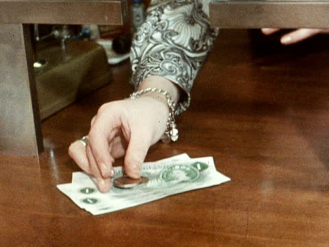 bank cashier hands a customer some pound notes and some new fifty pence pieces. 1969. - cashier stock videos & royalty-free footage