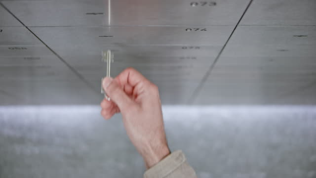 DS Bank clerk opening a safe deposit box to grant access to a male customer using his own key to unlock it