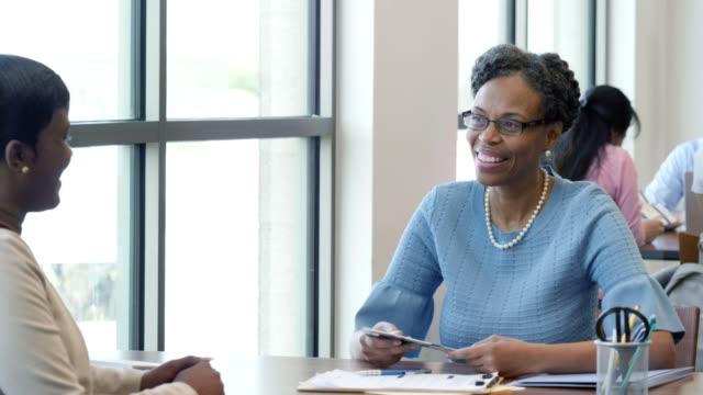 vídeos de stock, filmes e b-roll de funcionário bancário dá folheto informativo para o cliente feminino - folheto publicação