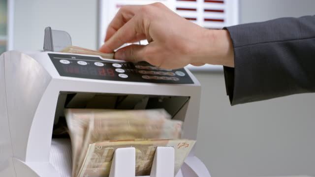 bank employee inserting  fifty euro banknotes into the automated currency counter - banknote stock videos and b-roll footage