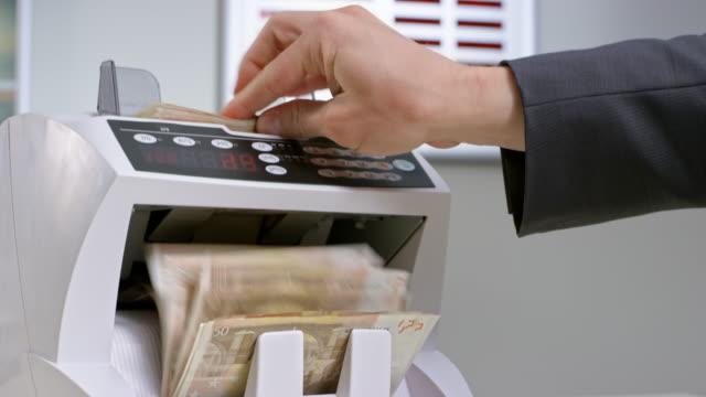 vídeos de stock, filmes e b-roll de funcionário do banco inserir notas de cinquenta euros em contador automatizado de moeda - nota de cinquenta euros