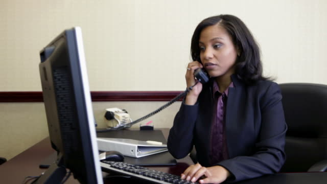 Bank manager using computer and answering telephone