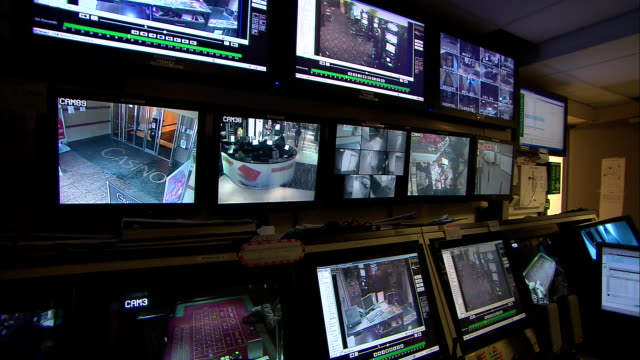 a bank of monitors shows several views inside a casino. - casino stock-videos und b-roll-filmmaterial